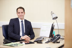 Portrait Of Male Consultant Working At Desk In Office Royalty Free Stock Photos
