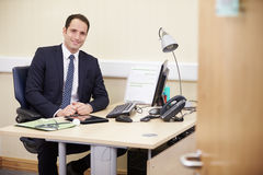 Portrait Of Male Consultant Working At Desk In Office Stock Image