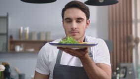 Man cook smelling salad at home kitchen. Cheerful chef presenting healthy food