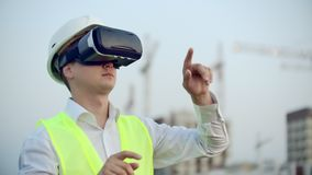 Portrait of a male crane operator operating a construction site using virtual reality glasses. Construction Manager. Manages the progress and plan of buildings stock video