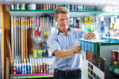 Portrait of male customer selecting paint can in housewares depa. Portrait of cheerful   smiling male customer selecting paint can in housewares department Stock Photo