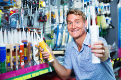 Portrait of  male customer selecting sealant bottle i Royalty Free Stock Images