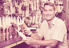 Portrait of  male customer selecting sealant bottle i. Portrait of  cheerful smiling male customer selecting sealant bottle in housewares department Stock Image