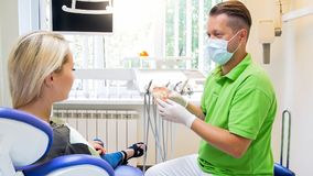 Portrait of male dentist talking to his patient and showing plastic jaw model. Portrait of dentist talking to his patient and showing plastic jaw model royalty free stock photo