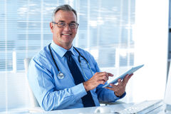 Portrait of male doctor with digital tablet in hospital. Portrait of smiling male doctor in eyeglasses using digital tablet in hospital Royalty Free Stock Image