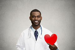 Portrait male doctor holding red heart. Closeup portrait happy, smiling male health care professional, man family doctor, cardiologist with stethoscope holding Royalty Free Stock Photo