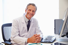 Portrait Of Male Doctor In Office Working At Computer Royalty Free Stock Photos