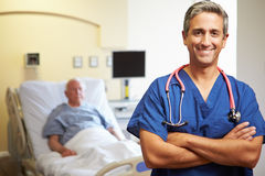 Portrait Of Male Doctor With Patient In Background. Portrait Of Male Doctor With Arms Crossed Smiling To Camera With Patient In Background Royalty Free Stock Photo