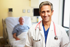 Portrait Of Male Doctor With Patient In Background. Portrait Of Happy Male Doctor With Patient In Background Lying Down In Bed Royalty Free Stock Photo