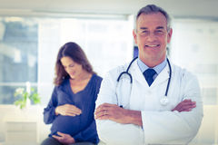 Portrait of male doctor with pregnant woman at clinic. Portrait of confident male doctor with pregnant women in background at clinic Stock Photos