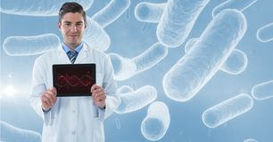 Portrait of male doctor showing DNA structure in tablet computer with microorganism structure in bac Royalty Free Stock Images