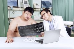 Doctor showing x-ray result to his patient Royalty Free Stock Photography