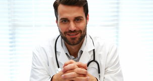 Portrait of male doctor sitting at desk stock video
