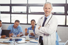 Portrait of male doctor standing with arms crossed. And colleagues discussing in background Royalty Free Stock Image