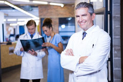 Portrait of male doctor standing with arms crossed. In hospital and colleagues standing behind and discussing Royalty Free Stock Images