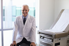 Portrait Of Male Doctor Wearing White Coat In Exam Room Stock Photo