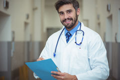 Portrait of male doctor writing on clipboard in corridor. At hospital Stock Image