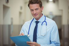 Portrait of male doctor writing on clipboard in corridor. At hospital Royalty Free Stock Photography