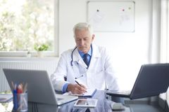 Senior male doctor working at desk in the specialist office. Portrait of male doctor writing down the diagnosis while sitting at consulting room Stock Photo