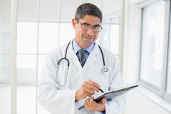 Portrait of a male doctor writing reports. Portrait of a smiling male doctor writing reports in the hospital Royalty Free Stock Images