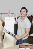 Portrait of male dressmaker holding sewing pattern, sketch and design draft Stock Photo