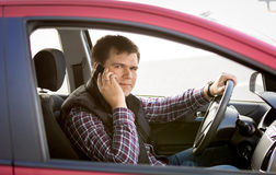 Portrait of male driver talking by phone while driving a car Royalty Free Stock Image