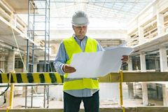 Portrait of male engineer at construction site. Building, development, teamwork and people concept stock photography