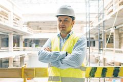 Portrait of male engineer at construction site. Experienced confident builder with arms crossed at a construction site. Building, stock image