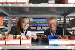 Portrait Of Male Engineer With Female Apprentice Checking Stock. Male Engineer With Female Apprentice Checking Stock Levels royalty free stock photos