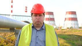 Portrait of a male engineer, nodding his head yes, and looking at the camera with power station in the background stock video footage