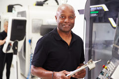Portrait Of Male Engineer Operating CNC Machinery In Factory Stock Photo