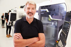 Portrait Of Male Engineer Operating CNC Machinery In Factory Stock Photography
