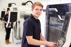 Portrait Of Male Engineer Operating CNC Machinery In Factory Stock Image