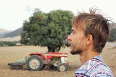 Portrait of male farmer in the background of old tractor standing in the middle of plowed field.Countryside in Cyprus royalty free stock image