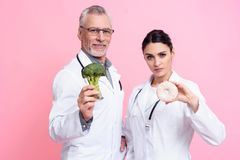 Portrait of male and female doctors with stethoscopes holding broccoli and donut isolated. Portrait of male and female doctors in white gowns with stethoscopes Stock Image