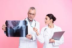 Portrait of male and female doctors with stethoscopes holding x-ray and clipboard isolated. Portrait of male and female doctors in white gowns with stethoscopes Stock Photos