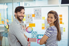 Portrait of male and female executives standing with arms crossed near whiteboard Stock Image