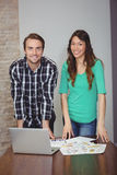 Portrait of male and female graphic designers standing in conference room Stock Photos
