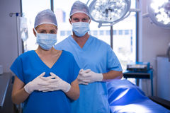 Portrait of male and female nurse wearing surgical mask in operation theater Royalty Free Stock Photos