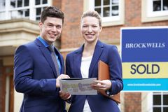 Portrait Of Male And Female Realtors Standing Outside Residential Property royalty free stock image