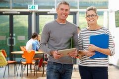 Portrait Of Male And Female Tutors In Classroom Stock Photo