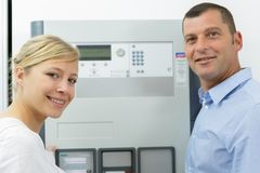 Portrait male and female workers by electronic machine stock image