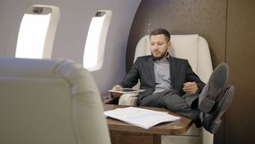 Portrait of male financial analytic relaxing in the private entrepreneur jet. Concept of: lawyer, business people, paper work, confortable seat stock video footage