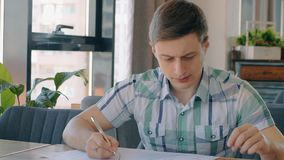 Portrait of male financial analytic working in cafe, slow motion. Concept of: cafe table, hand writing, paper work stock video
