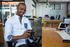 Portrait of male graphic designer holding digital camera at desk stock photo