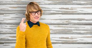Portrait of male hipster crossing fingers against wooden wall Royalty Free Stock Photography