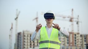 Portrait of a male inspector analyzing the work of builders using virtual reality glasses. A man in a helmet and a stock video footage