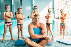 Portrait of male instructor with children. Near swimming pool. Cute boys with swimming goggles stands near water. Healthy and happy childhood concept Royalty Free Stock Photo
