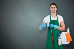 Male Janitor Holding Cleaning Equipments. Portrait Of A Male Janitor Holding Cleaning Equipments On Gray Background Royalty Free Stock Photo