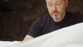 Portrait of male masseur with a beard doing lumbar massage in spa salon